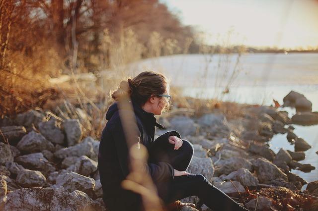 Woman sitting by lake.